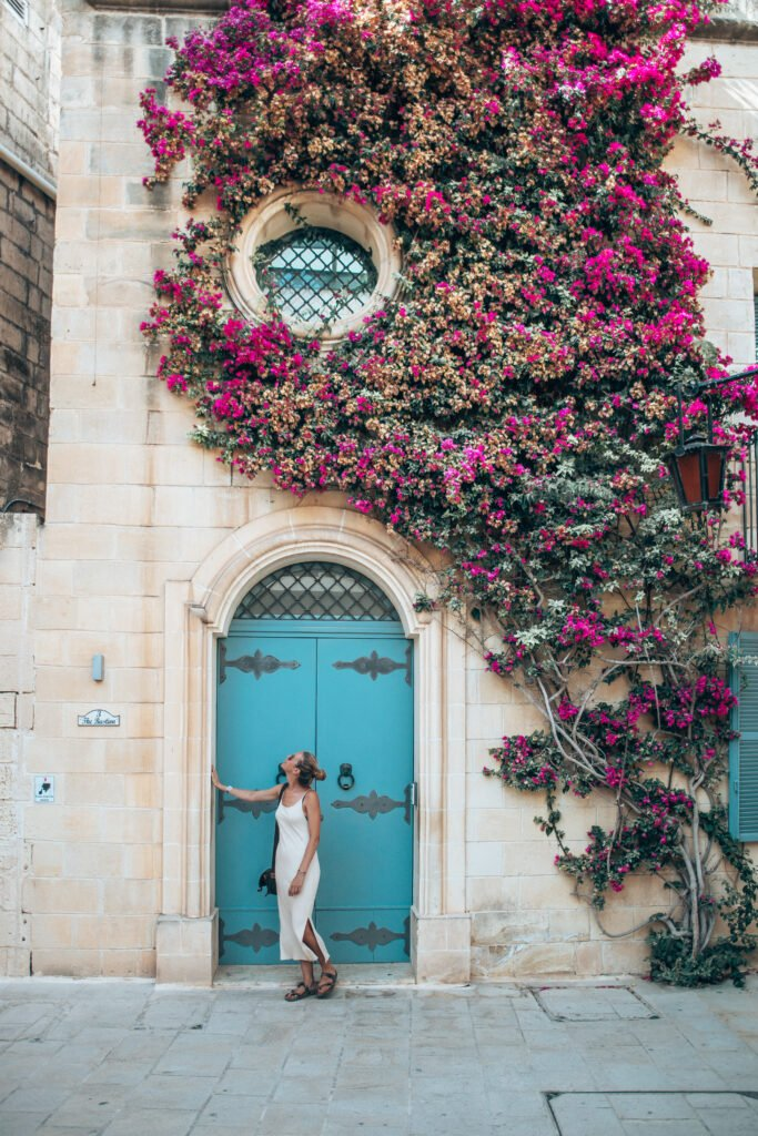 Ancient doors of Malta with colourful flowers