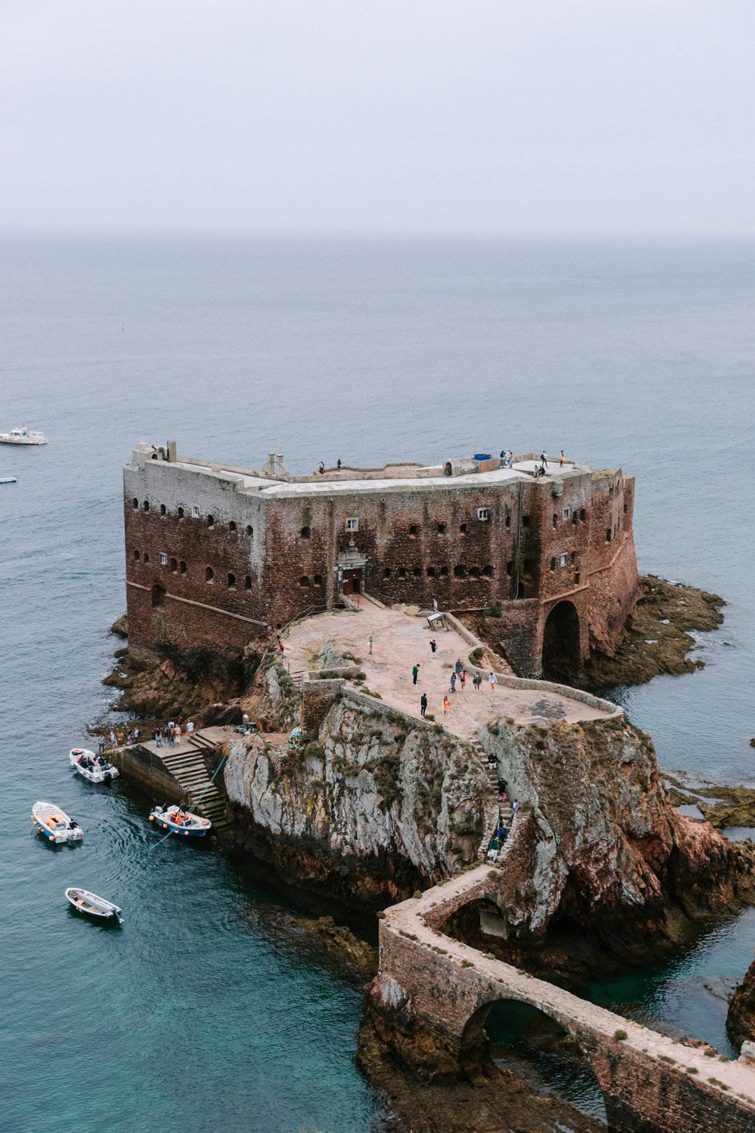 A view of the São João Baptista Fortress from on top of the cliff with people walking on the water passage and fishing boats on the Portugal island Berlenga Grande