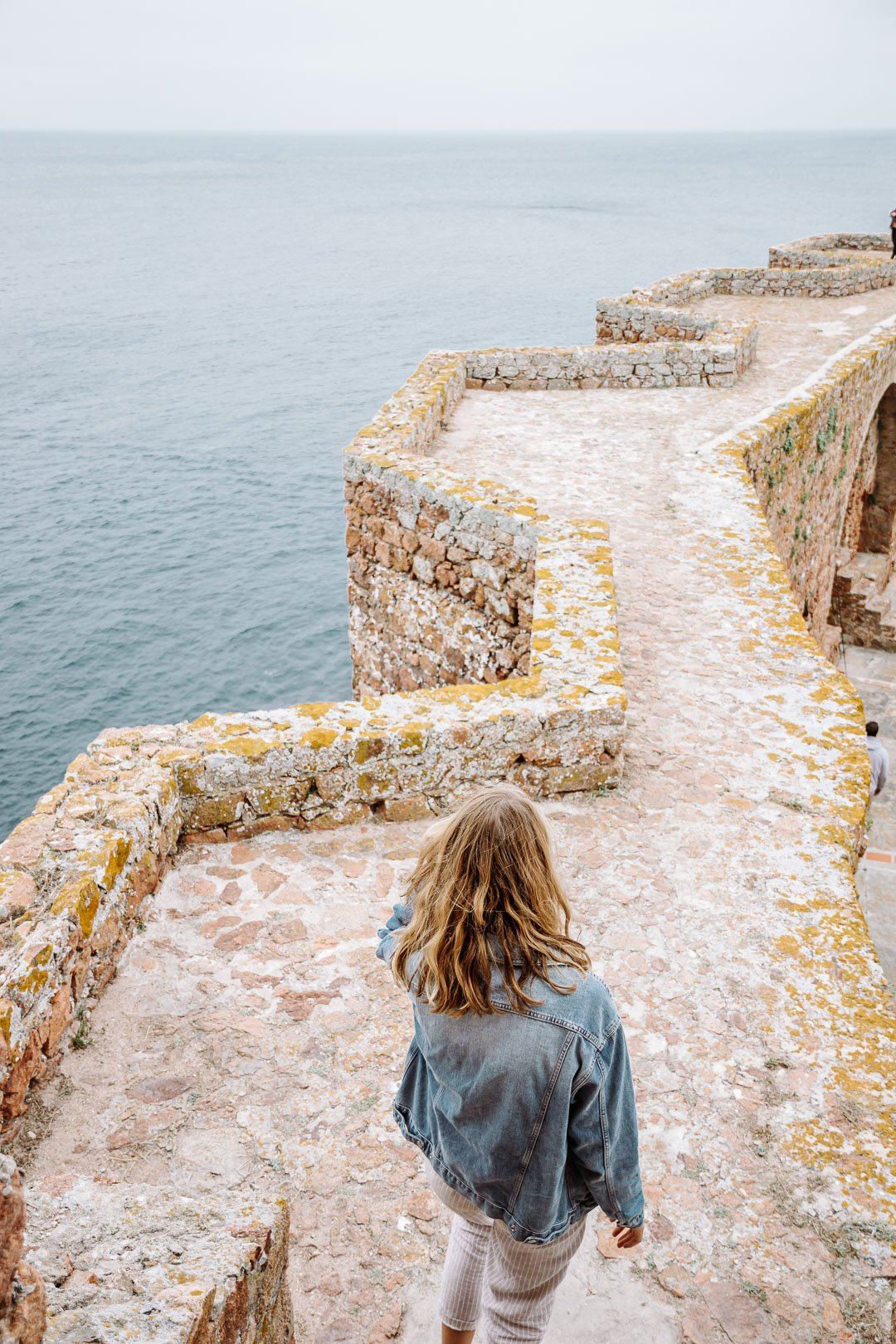 A girl walking the wall at the São João Baptista Fortress