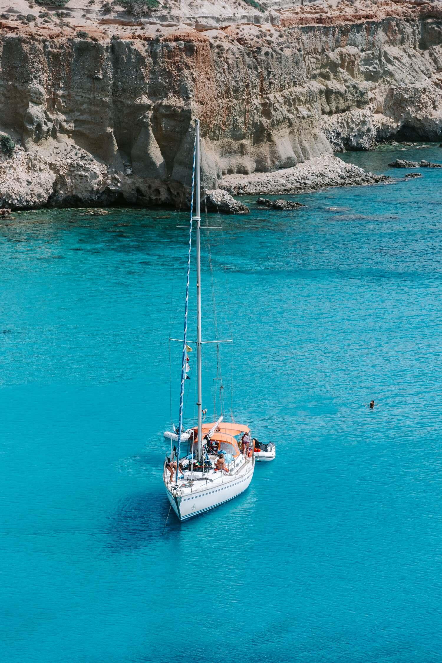 A yacht anchored at Tsigrado Beach one of the best Milos Beaches