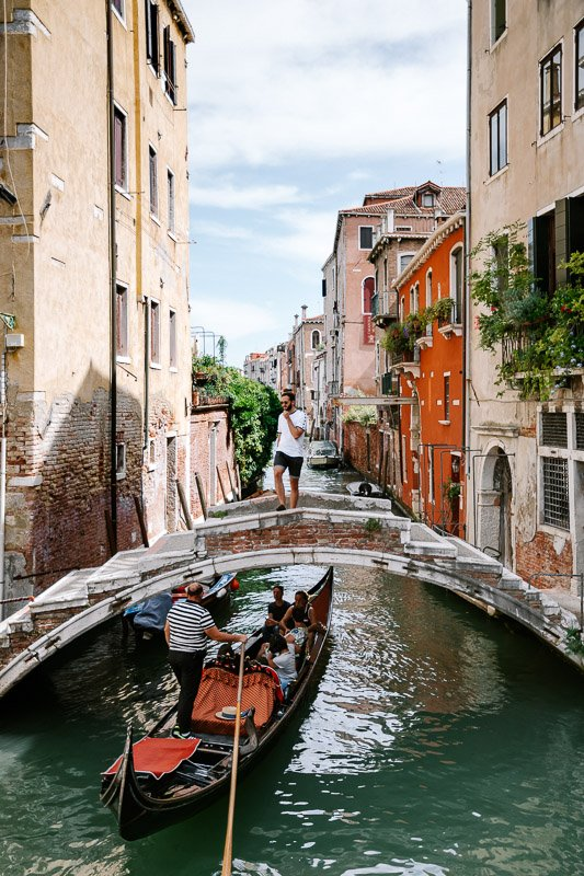A back street within Venice leading towards a Venice Canal showing the colourful architecture and one of the many small bridges crossing the canals and gondola