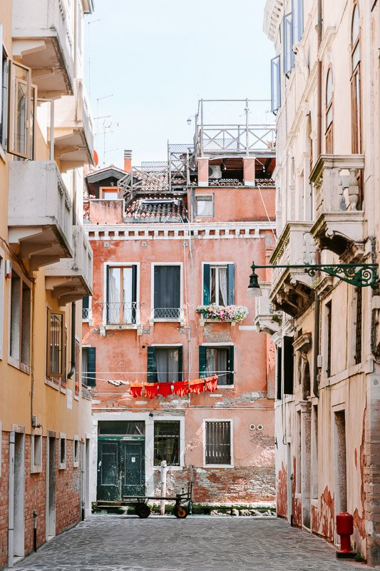 A back street within Venice leading towards a Venice Canal showing the colourful architecture an clothes hanging between the houses