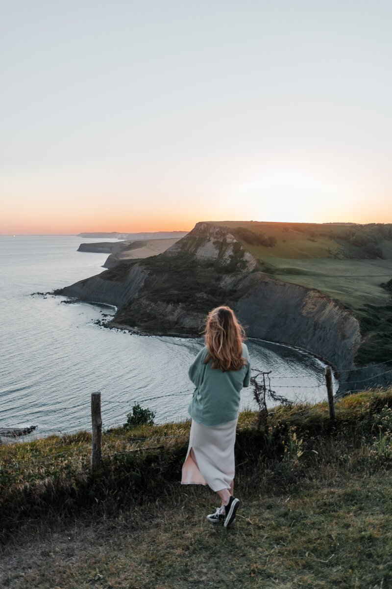 Girl looking out over a sunset over Chapmans Pool on the Jurassic Coast