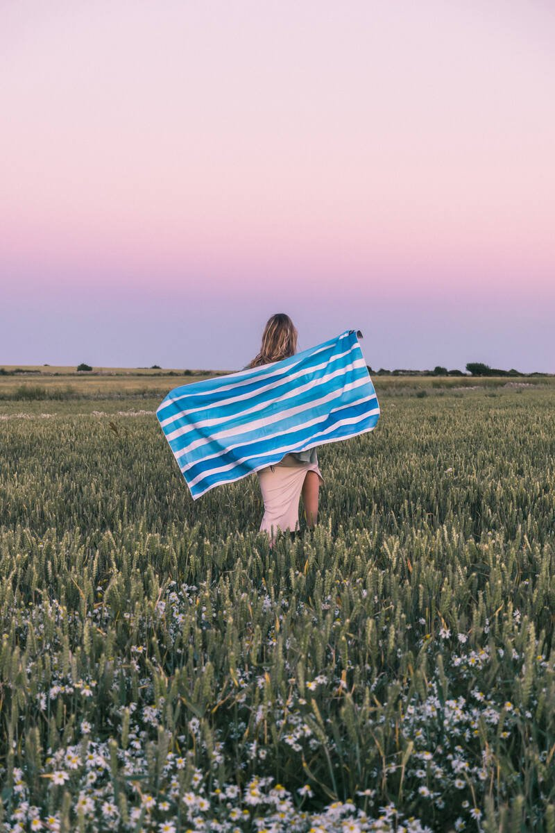 Girl standing in a field at Chapmans Pool which is one of the best places to visit on Dorset Jurassic Coast