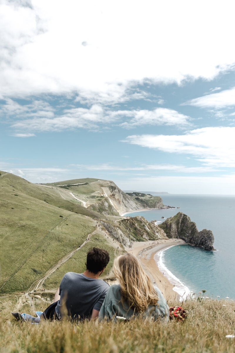 Couple sitting having a picnic looking over Durdle Door on the Jurassic Coast
