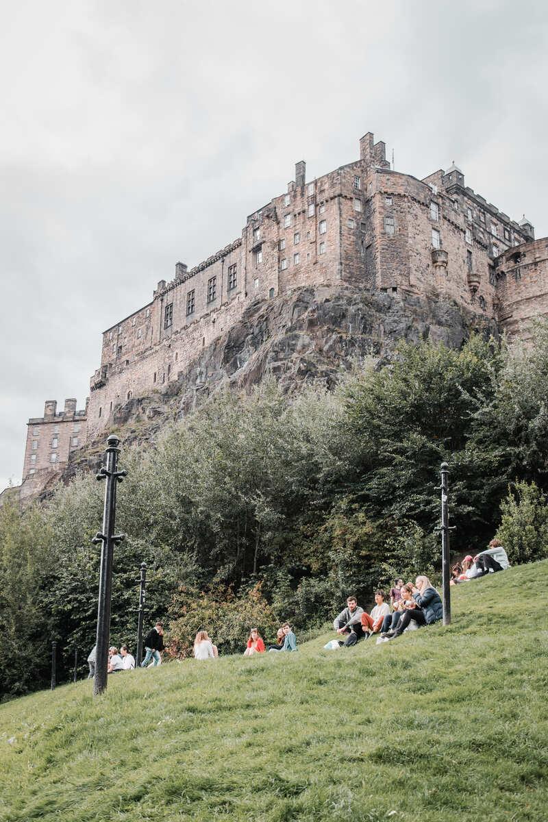 Groups sitting below Edinburgh castle during what to visit in Edinburgh