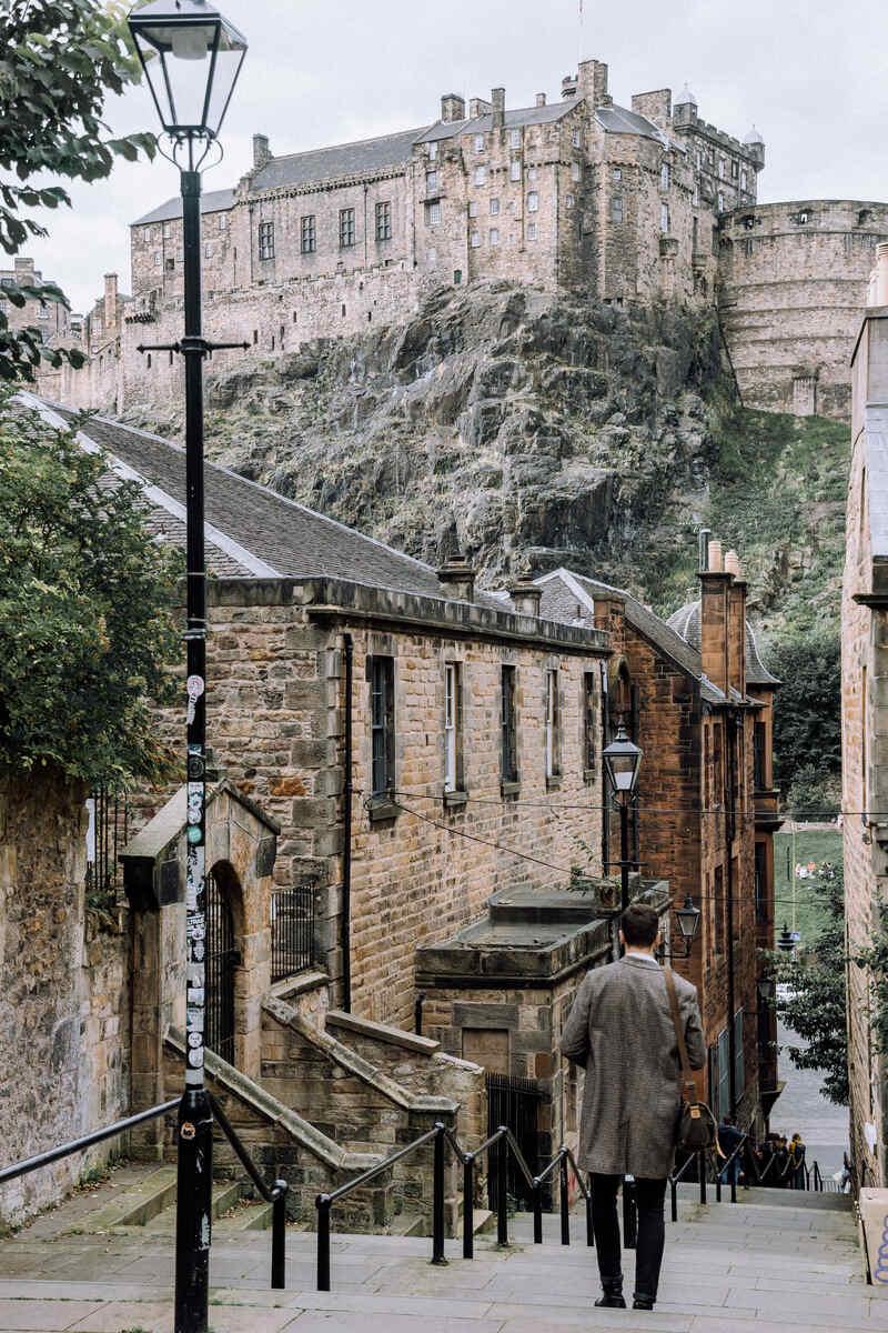 Man walking down staircase towards Edinburgh Castle